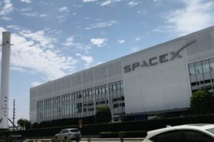 SpaceX building in Hawthorne, California with on its left a Falcon rocket.